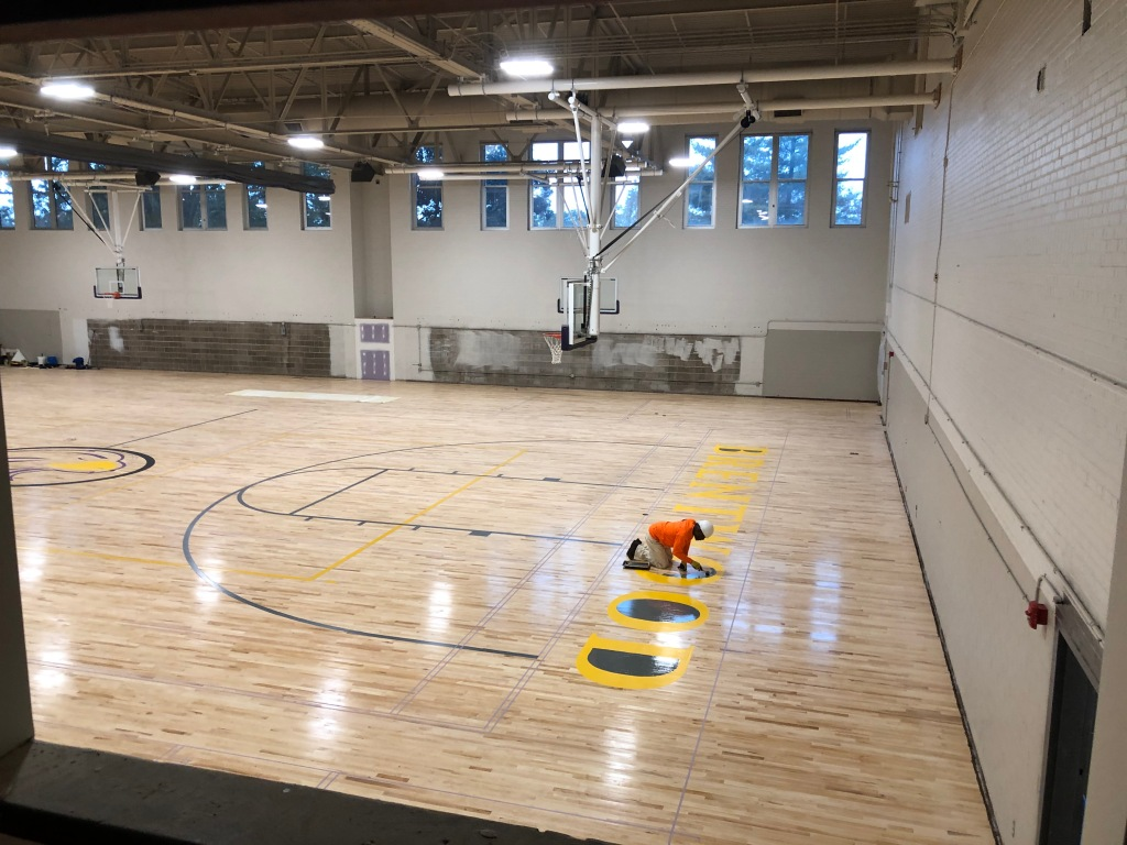 Large gym being striped and painted.